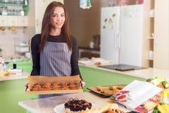 Ståenden av kakor och kakor för kvinnlig kock som stekheta står le på kameravisningen, ny-bakade bakelse royaltyfria bilder