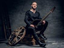 Ståenden av keltisk kläder för traditionell tappning för spelmannen iklädd sitter på en träask och rymmer mandolinen fotografering för bildbyråer