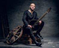 Ståenden av keltisk kläder för traditionell tappning för spelmannen iklädd sitter på en träask och rymmer mandolinen royaltyfri foto