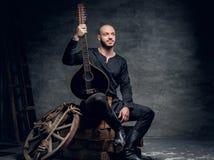 Ståenden av keltisk kläder för traditionell tappning för spelmannen iklädd sitter på en träask och rymmer mandolinen royaltyfri bild