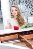 Ståenden av kvinnan med bordeaux steg spela pianot royaltyfri bild