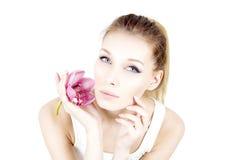 Ståenden av kvinnan med hållande rosa färger för permanent smink blommar och den rörande kinden Royaltyfria Foton