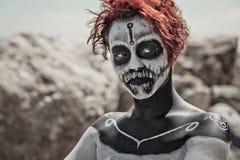 Ståenden av kvinnan med röd hår- och sminkallhelgonaafton utformar arkivfoto