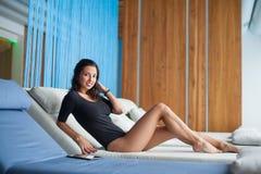 Ståenden av kvinnlign med perfekt hud i svart bodysuit ligger på den vita dagdrivaren på vardagsrumzonen i brunnsortsemesterorten arkivbilder