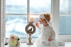 Ståenden av lite behandla som ett barn flickor som är blonda i vitt klänningsammanträde på a royaltyfri foto