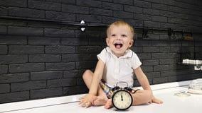Ståenden av lite behandla som ett barn pojkesammanträde på köksbordet med klockan bredvid honom som stänger hans le för ögon Ha g lager videofilmer