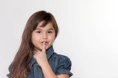 Ståenden av litet att le att göra en gest för liten flicka hyssjar ner Arkivfoton