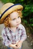 Ståenden av lockigt rödhårigt behandla som ett barn i en hatt Royaltyfri Bild