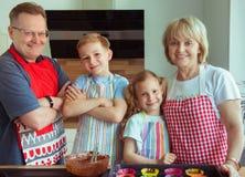 Ståenden av lyckliga morföräldrar har gyckel med deras barnbarn Arkivbild