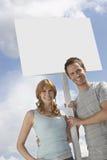 Ståenden av lyckliga par med tomt undertecknar över molnig himmel Royaltyfri Fotografi