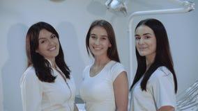 Ståenden av lyckliga säkra tandläkare ser kameran på tand- rum stock video