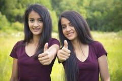 Ståenden av lyckliga systrar kopplar samman upp visningtummar Arkivfoton
