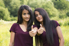 Ståenden av lyckliga systrar kopplar samman upp visningtummar Royaltyfri Bild