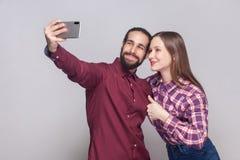 Ståenden av lyckliga tillfredsställda par som står, ser och ler på kameran av den mobila smarta telefonen för att göra selfie ell arkivfoton