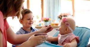 Ståenden av lyckligt barn behandla som ett barn i hög stol som matas royaltyfri fotografi