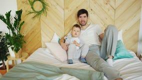 Ståenden av lyckligt stiligt barn avlar och hans son som ligger på säng som ler och poserar in i kamera Royaltyfri Fotografi