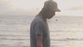 Ståenden av mannen i hörlurar arbetar avläsande sand på stranden med metalldetektorn som finner värdesaker på soluppgång lager videofilmer