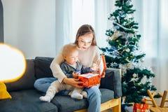 Ståenden av modern och behandla som ett barn nära julgranen, det lyckliga feriebegreppet, familj Fotografering för Bildbyråer
