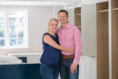 Ståenden av mogna par som nytt lyxigt kök är hemma Fitte royaltyfria foton
