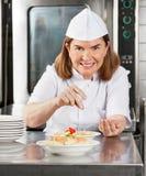 Mogna den kvinnliga kocken som garnerar maträtten Fotografering för Bildbyråer