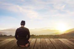 Ståenden av muslim man att knäfalla och att be till guden royaltyfri foto