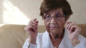 Ståenden av mycket den pålagda gamla kvinnan och tar av exponeringsglas, ultrarapid lager videofilmer