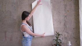 Ståenden av ny ägarekvinnan av lägenheten gör reparationer och att rymma en rulle av tapeten nära den tomma väggen inomhus