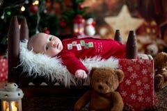 Ståenden av nyfött behandla som ett barn i jultomten som kläder in behandla som ett barn lite säng Royaltyfri Foto