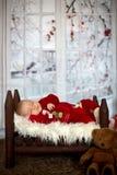 Ståenden av nyfött behandla som ett barn i jultomten som kläder in behandla som ett barn lite säng Arkivfoton