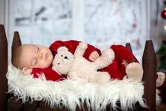 Ståenden av nyfött behandla som ett barn i jultomten som kläder in behandla som ett barn lite säng Royaltyfri Bild