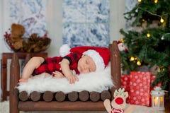 Ståenden av nyfött behandla som ett barn i jultomten som kläder in behandla som ett barn lite säng, sl Royaltyfri Fotografi