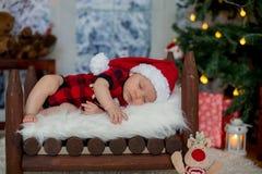 Ståenden av nyfött behandla som ett barn i jultomten som kläder in behandla som ett barn lite säng, sl Arkivbilder