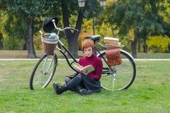 Ståenden av rödhårig mandamen i parkerar med cykeln arkivfoton