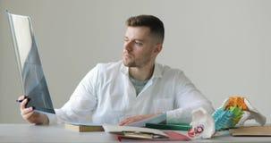 Ståenden av roentgenologisten gör hans skrivbordsarbetehandstilbeskrivning av röntgen- sammanträde på hans arbetsplats lager videofilmer