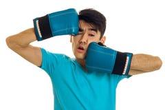 Ståenden av roliga brunettsportar man den praktiserande asken i blåa handskar som isoleras på vit bakgrund Arkivbild