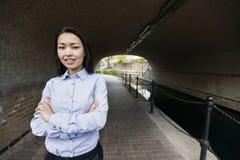 Ståenden av säkra asiatiska affärskvinnaanseendearmar korsade vid kanalen royaltyfri fotografi