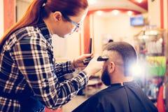 Ståenden av stiligt barn uppsökte den caucasian mannen som får moderiktig frisyr i modern barberare, shoppar Royaltyfri Bild