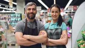 Ståenden av två attraktiva personer för supermarketanställda i förkläden som står insidan, shoppar, ler och ser kameran stock video