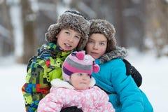 Ståenden av två gladlynta lyckliga pojkar och behandla som ett barn flickan i vinter parkerar Arkivfoto