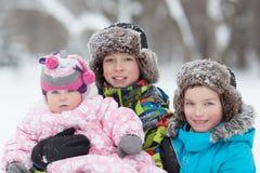 Ståenden av två gladlynta lyckliga pojkar och behandla som ett barn flickan i vinter parkerar Royaltyfri Fotografi