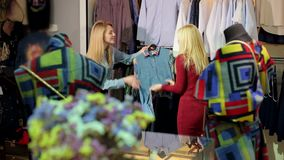 Ståenden av två härliga unga kvinnor som shoppar i kläder, shoppar stock video