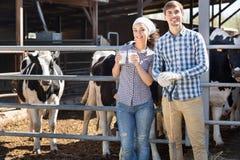 Ståenden av två jordbruksarbetare som rymmer som är glass med, mjölkar Arkivfoto