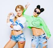 Ståenden av två moderiktiga kalla hipsterflickor i ljus limefrukt och whigte utrustar, moderiktiga frisyrer och makeup, solglasög Arkivbild