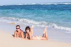 Ståenden av två unga kvinnliga vänner ligger på havskusten som ser kameran och att skratta Caucasian unga kvinnor Arkivbilder