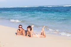 Ståenden av två unga kvinnliga vänner ligger på havskusten som ser kameran och att skratta Caucasian unga kvinnor Royaltyfria Bilder