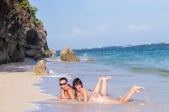 Ståenden av två unga kvinnliga vänner ligger på havskusten som ser kameran och att skratta Caucasian unga kvinnor Arkivbild