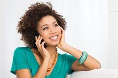 Lycklig kvinna som talar på mobiltelefon arkivbild