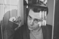 Ståenden av ungt olyckligt deprimerat ensamt se för man belastade att luta på fönstret hemma arkivfoton