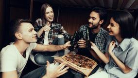 Ståenden av vänner som tillsammans kopplar av, äter pizza royaltyfri bild