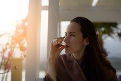 Ståenden för kvinna` s i en poncho har te på en öppen terrass på kusten med en signalljus från solen arkivbilder